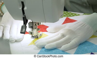 Hands seamstress in white gloves, which sews fabric on the...
