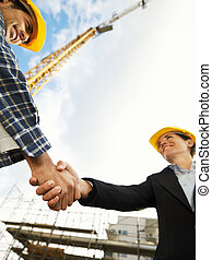 hands shaking - female architect and construction worker...