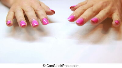 Hands showing fresh pink manicure at the nail salon