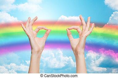 hands showing ok sign over rainbow background