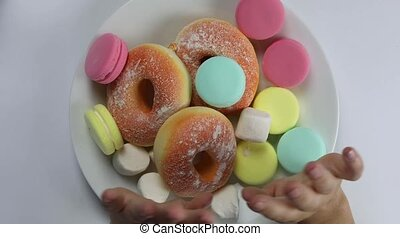 Hands showing stop sign pushing away rejecting donut,macarons,fastfood and sugar on white plate top view, health weightloss concept colorful