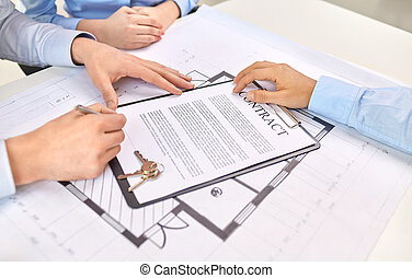 hands signing property purchase contract at office
