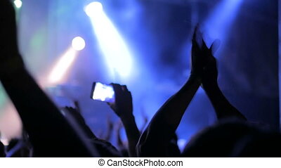 Hands silhouette recording video of live music concert with...