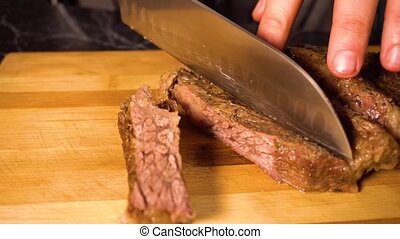Hands slicing cooked beef meat on a cutting board - Close up...