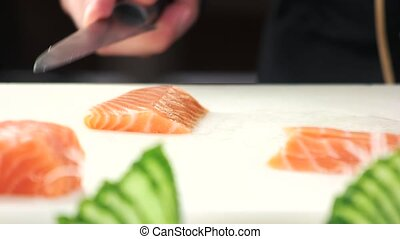 Hands slicing fish close up. Raw salmon on cutting board.
