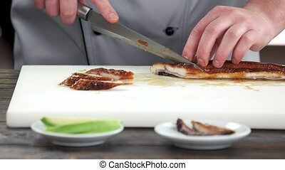 Hands slicing fish. Smoked eel on cutting board.