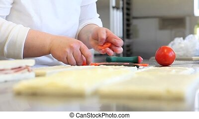 hands slicing tomato for sandwich