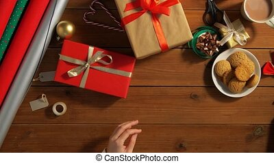 hands stacking packed christmas gifts on table - holidays, ...
