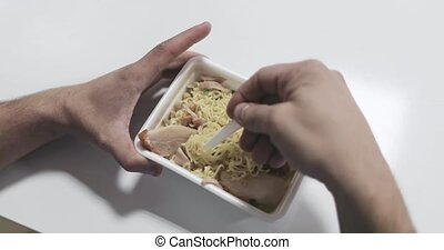 hands stir instant noodles plastic fork top view.