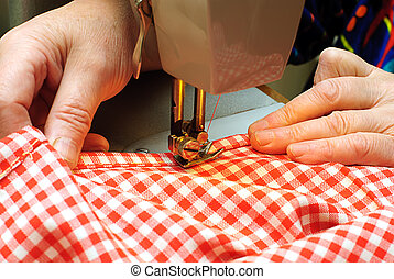Hands stitching denim cloth with a sewing machine