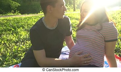 Hands stroking pregnant belly. Husband's hands stroking belly of his pregnant wife. Soft sunset sun illuminates the scene