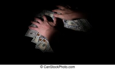 Hands take lot of money on a black background