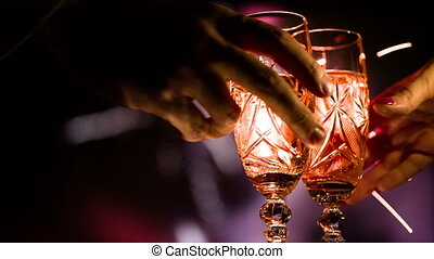 Hands take two glasses of champagne and clink glasses put...
