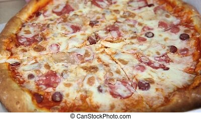 Hands takes a slice of pizza top view shot.