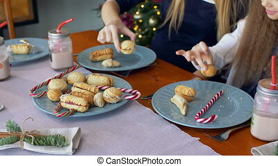 Hands taking christmas cookies and candy from plate -...