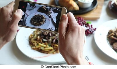 Hands taking photo various dishes with smartphone. Close up.