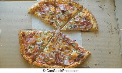 Hands taking pieces of pizza from a cardboard box - Hands...