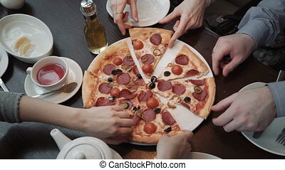 Hands taking pizza cuts Top view, close-up shot. In a cafe, communication and friends