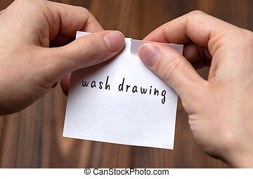 Concept of cancelling. Hands closeup tearing a sheet of paper with inscription wash drawing