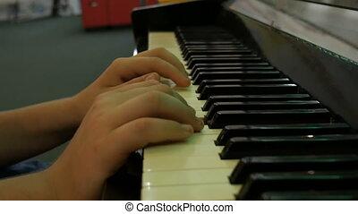 Hands teenage boy playing piano keys close up view - Hands...