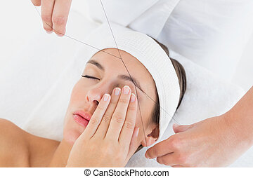 Hands threading beautiful woman's eyebrow - Close up of a...