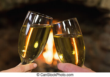 Hands toasting champagne flutes in front of fireplace