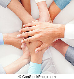 Hands Together - A group of people showing their unity by...
