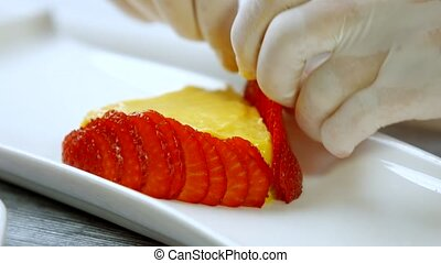 Hands touch slices of strawberry. Pieces of berry around...
