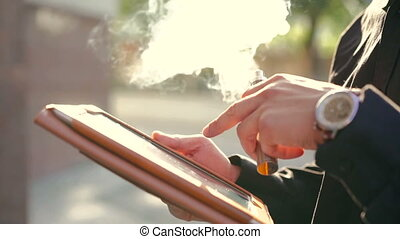 Hands touching tablet screen and smoking e-cigarette on the street