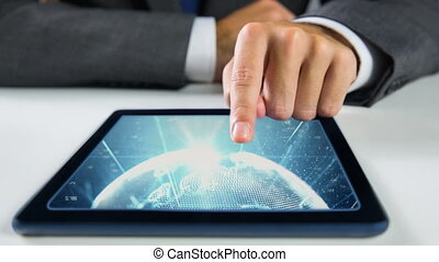 Hands touching tablet showing world video