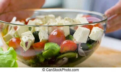 hands turning bowl of vegetable salad with feta - healthy ...