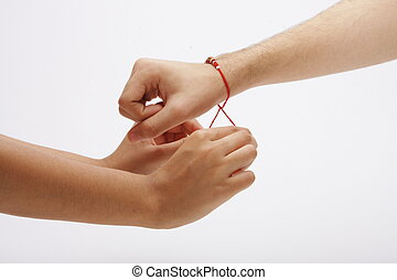 Hands tying a sacred thread - Horizontal close studio shot...