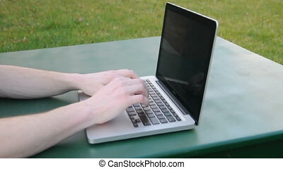 Hands type on a laptop that is resting on a green table...