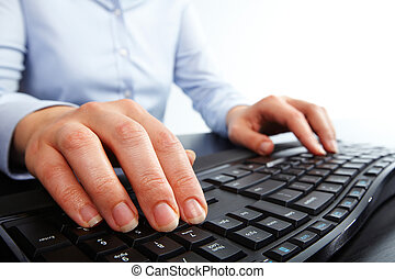 Hands typing on computer keyboard.