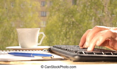 Hands typing on keyboard, outdoors