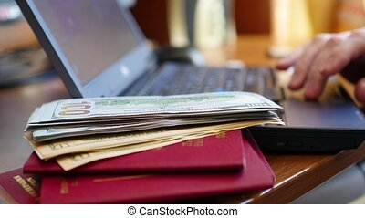 Hands typing text on laptop, close-up of money and passports
