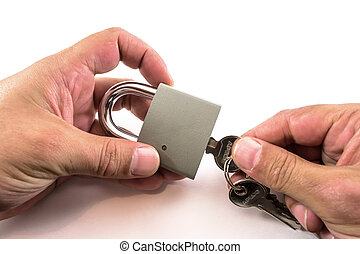 Two hands unlocking with a key a grey metal padlock