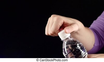 Hands up and opening a white bottle of fresh water on dark, slow motion, splash, spray, bubbles