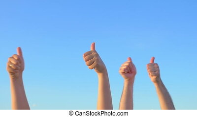 Hands up with thumbs-up against blue sky - Slow motion of...