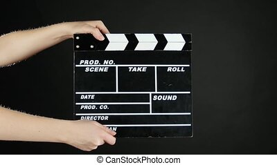 Hands use movie production clapper board, on black
