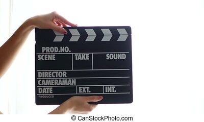 Hands using a film clapper board, close up.