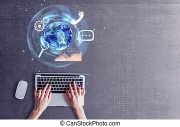 Hands using laptop with globe