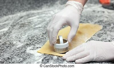 Hands using ravioli cutter. Food preparation, stuffed dough.