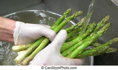 Hands washing asparagus close up. Fresh vegetable, green...