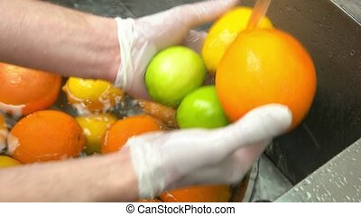 Hands washing citrus fruits. Orange, lime and lemon.