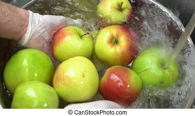 Hands washing fresh apples. Fruit in water.