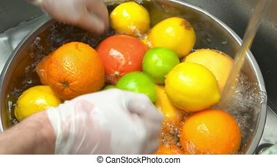 Hands washing fresh fruits.