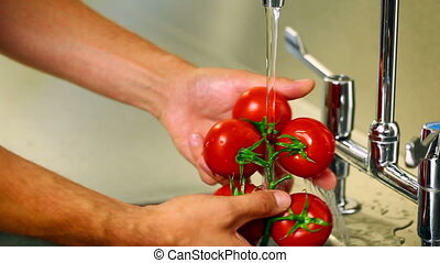Hands washing tomatoes under the tap