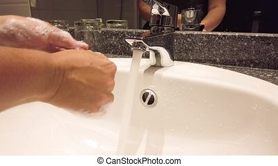 Woman open tap and washing hands using sanitizer under flowing water in clean and modern bathroom