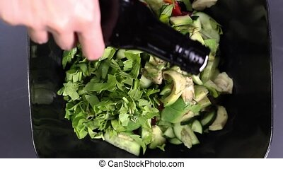 Hands watering salad with vegetable oil close-up. Top view...